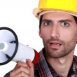 Stock Photo: Young laborer with bullhorn in hand