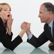 Blond woman arm wrestling her boss — Stock Photo #10084912