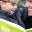 Man with little boy reading book outdoors — Stock Photo