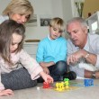 Elderly couple playing with their grandchildren — Stock Photo