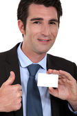 Man giving ok gesture whilst holding business card — Stock Photo