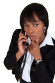 Suspicious woman talking on the phone — Stock Photo