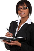 Una mujer de negocios tomando notas en un planificador. — Foto de Stock