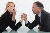 Blond woman arm wrestling her boss — Stock Photo