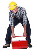 Laborer lifting heavy toolbox — Stok fotoğraf