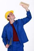 Pedreiro jovens segurando o tijolo e a colher de pedreiro — Foto Stock