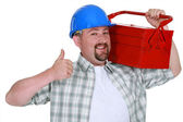 Tradesman carrying a toolbox and giving the thumb's up — Stock Photo