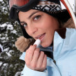 Stock Photo: Skier applying lip balm