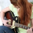 Redhead girl playing guitar - Stock Photo