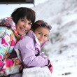 Mother and daughter stood by chalet — Stock Photo