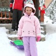 Stock Photo: Couple posing with daughter near chalet at ski resort