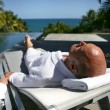 Old man laying on poolside sun lounger - Stock Photo