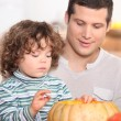 Child emptying pumpkin — Stock Photo