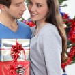 Young man offering gift to his girlfriend for Christmas — Stock Photo #10095401