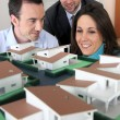 Architect showing model housing to customers - Stock Photo