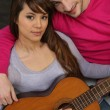 Couple sat with acoustic guitar — Stock Photo #10096505