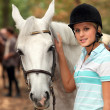 Girl stroking white horse — Stockfoto #10096953