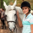 Girl stroking white horse — Stock Photo #10096953