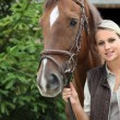 Blonde girl with horse - Stock Photo