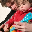 Stock Photo: Boy and father plying with toy guitar
