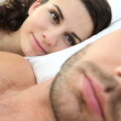 Woman looking at man in bed — Stock Photo