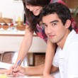 Couple writing on kitchen table — Stock Photo #10099623