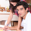 Couple writing on the kitchen table — Foto Stock