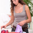 Woman searching through shopping bags - Stockfoto