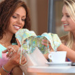 Stock Photo: Two girls look them at purchases