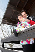 Couple stood by snow covered chalet — Stock Photo