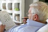 Starší muž dělá křížovky — Stock fotografie