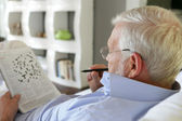 äldre man gör korsord — Stockfoto