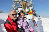 Father and daughter stood by snowman — Stock Photo