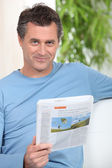 Smiling man reading newspaper on a couch — Stock Photo