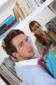 Male and female students in library — Stock Photo