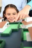 Child looking at a model of a housing estate — Stock Photo