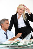 A boss and his female assistant thinking behind a subdivision model — Stock Photo