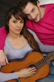 Couple sat with acoustic guitar — Stock Photo
