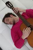 Homem em um sofá com uma guitarra — Foto Stock