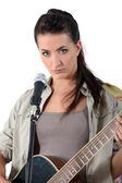 Young woman singing and playing guitar — Stock Photo