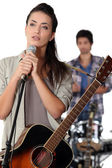 Brunette with microphone rehearsing — Stock Photo