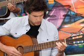Musician with guitar in front of painted wall — Stock Photo