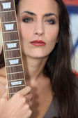 Unfriendly woman posing with her guitar — Stock Photo