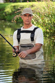Fisherman wading in river — Stock Photo
