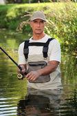 Fisherman wading in river — Stock Photo