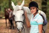 Girl stroking white horse — Stock Photo