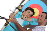 A father teaching his son how to shoot bow. — Stock Photo