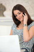 Woman with computer on the phone — Stock Photo