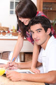 Couple writing on the kitchen table — Stock Photo