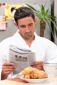 Man having breakfast with newspaper — Stock Photo